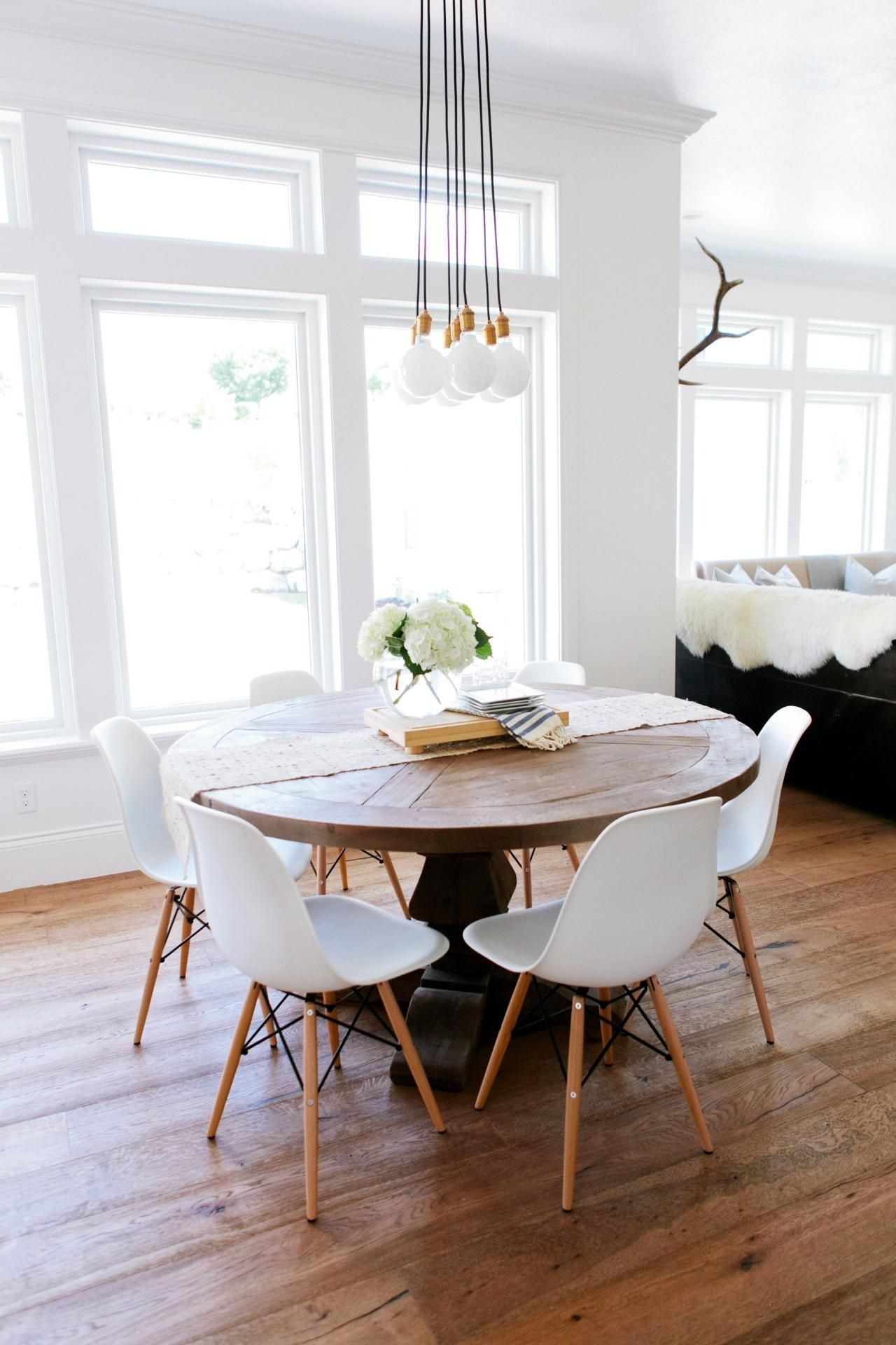 A Rustic Round Wood Table Surroundedwhite Eames Dining Chairs Creates An Interesting Mix In